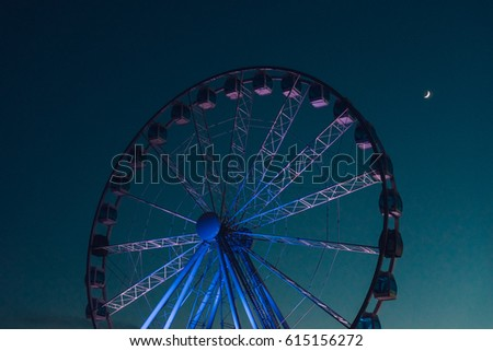 Inactive ferris wheel against dark evening sky with half moon