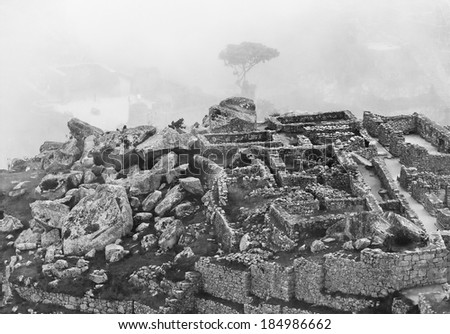 Inca city Machu Picchu in mist weather. It is a designated UNESCO World Heritage Site - Peru, South America (black and white) - stock photo