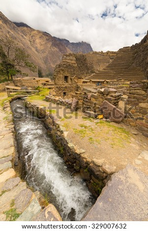 Inca's water canal in the archeological site of Ollantaytambo, Sacred Valley, major travel destination in Cusco region, Peru. Inca terraces in the background. - stock photo