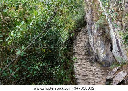 Inca trail passing through the ruins of Machu Picchu, Cusco Region, Urubamba Province, Machupicchu District, Peru - stock photo