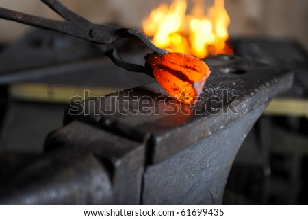 Incandescent element in the smithy on the anvil - stock photo