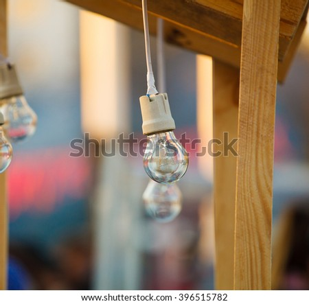 incandescent light bulbs hanging on wires and trees - stock photo
