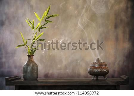 Incense burner and bamboo leaf on table, Zen concept. - stock photo
