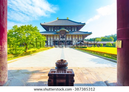 Incense burner and pillars in foreground leading to front facade of the Great Buddha Hall Daibutsuden at Todai-ji temple on a beautiful blue sky morning with nobody present in Nara, Japan. Horizontal - stock photo