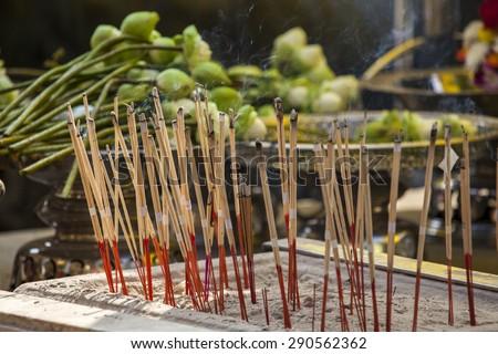 Incense burning at the Emerald Buddha Temple in Bangkok - stock photo