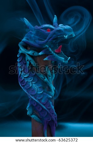 Incense stick inside wooden dragon. - stock photo