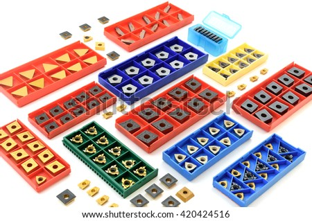 incisors in colorful boxes, metal and golden lathe tools for heavy industry on white background - stock photo