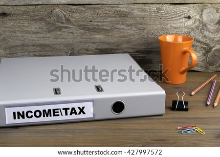 Income and Tax - folder on wooden office desk - stock photo