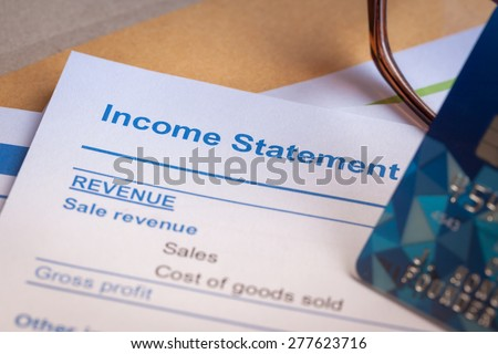 Income statement letter on brown envelope and eyeglass, business concept; document is mock-up