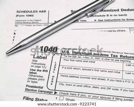 Income tax forms and a pen on a table.