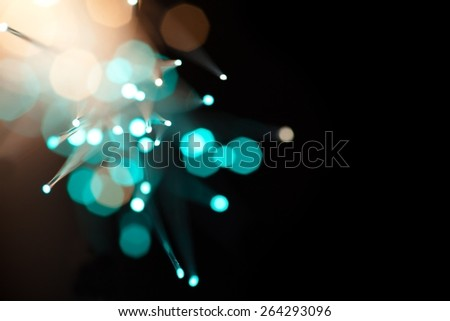 Incoming light through fiber optics abstract background. Soft focus, bokeh background. Intentionally shot with lens flares. - stock photo