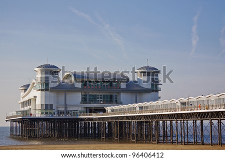 Incoming tide under the traditional seaside pier at Weston-super-mare UK - stock photo