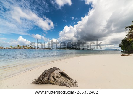 Incoming tropical stormy weather in the remote Togean Islands, Central Sulawesi, Indonesia. White sandy beach and the blue lagoon, with scenic clouds, islets and fishermen village in the background. - stock photo
