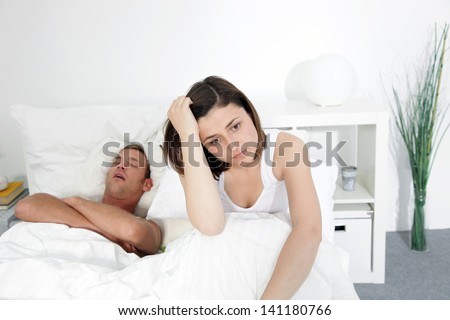 Incompatibility in bed with a husbands loud snores preventing his wife from getting any sleep and rest - stock photo