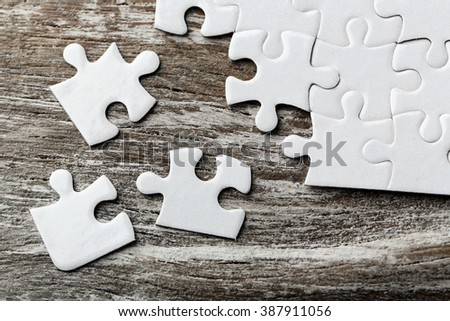 Incomplete puzzles on wooden table - stock photo