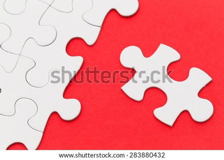 Incomplete white puzzle with red color background with copyspace - stock photo