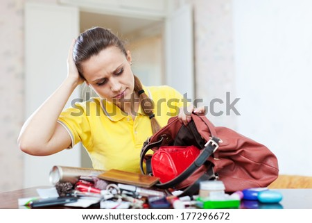 Inconsiderate woman lost something and looking in her purse - stock photo