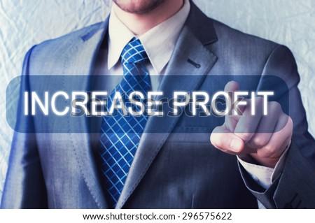 Increase Profit. Businessman touching button on virtual screen - stock photo