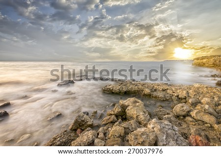 Incredible sunset . The rocky bay of the sea - stock photo