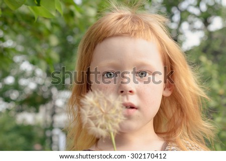 incredibly beautiful red-haired girl with big eyes holding a dandelion - stock photo