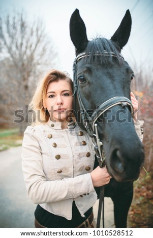 Incredibly beautiful woman with luxurious hair walks with a horse