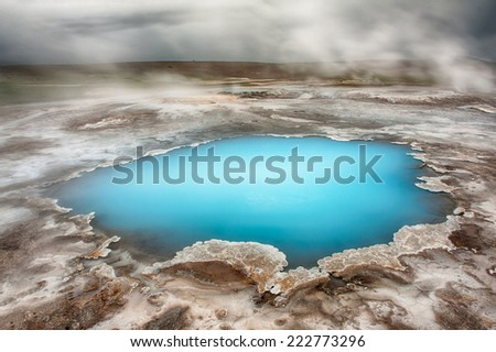 Incredibly blue pool Blahver at Hveravellir is actually a hot geothermal spring in the heart of Iceland. Photo taken around midnight with a storm coming  - stock photo