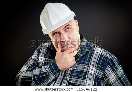 Incredulous worker with helmet. Hand on chin, black background. - stock photo