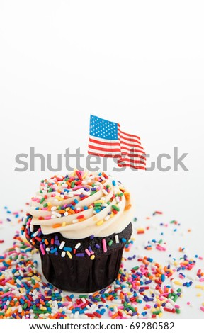 Independence Day Themed Cupcake with Lots of Red, White and Blue  Sprinkles plus US Flag - stock photo