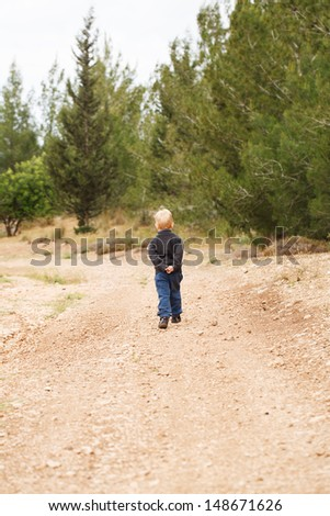 Independent little boy goes to nature - stock photo