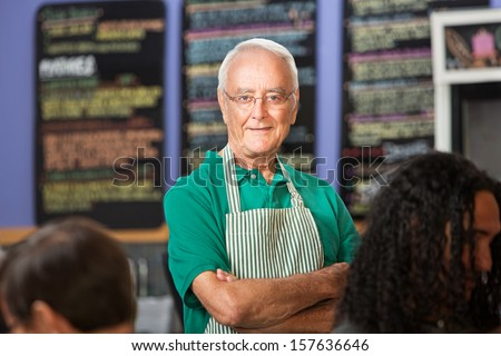 Independent older cafe employee with striped apron - stock photo