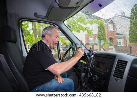 Independent senior in retirement setting up satellite navigation in his transport van - stock photo