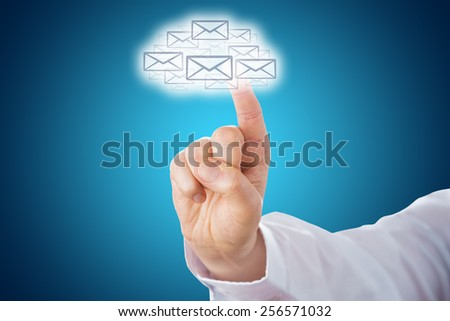 Index finger pointing at a cloud computing icon shaped out of a host of email letter symbols. The cloud shape is highlighted over a blue background. Metaphor for connectivity in cyberspace. Close up. - stock photo