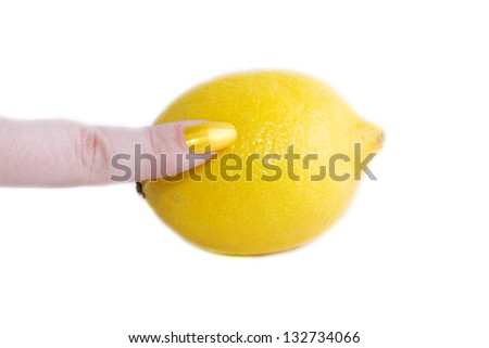 Index finger with yellow varnish is on the lemon