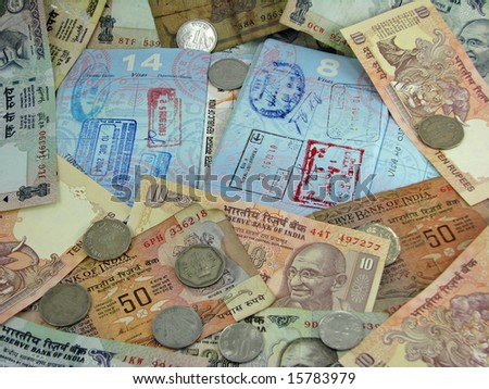 India currency on top of passports with visas. - stock photo