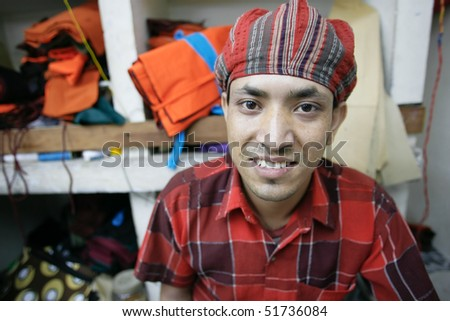 INDIA - FEB 26: Young textile worker in a small factory in Old Delhi on February 26, 2008 in Delhi, India. Many small factories provide the West with their clothes. - stock photo