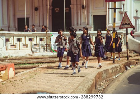 INDIA, GOA - circa 2012: Unidentified hindu school children dressed in uniform go home after classes - stock photo