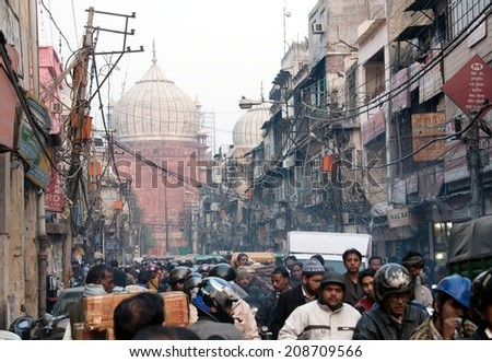 INDIA, OLD DELHI, 5th of December 2010 - Overcrowded street in old town with smog, dangerous electric lines and Jama masjid  - stock photo