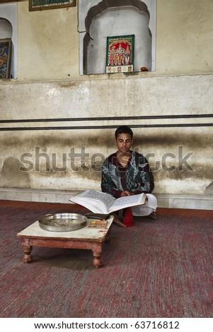 India, Rajasthan, Jaipur, an indian boy reads a religious book in an hindu temple near Sisodia Rani Ka Bagh Palace - stock photo