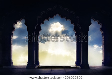 Indian arch silhouette in old temple at dramatic sunset sky with light hole in the clouds - stock photo