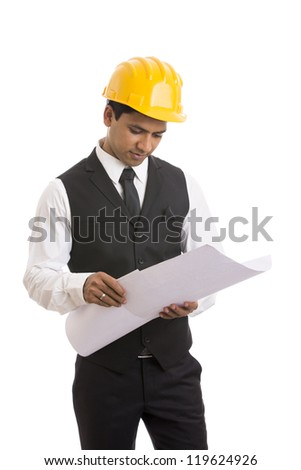 Indian Architect holding and looking the blueprints - stock photo