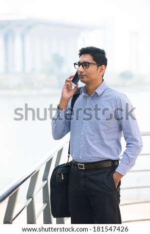 indian asian business male with cell phone and lake background - stock photo