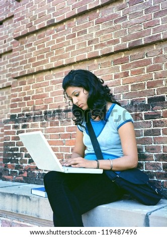 Indian / Asian college girl / student working on laptop computer in the campus. - stock photo