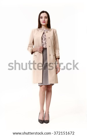indian asian eastern brunette business executive woman with straight hair style in pastel pink trench-coat high heels shoes full length body portrait standing isolated on white - stock photo