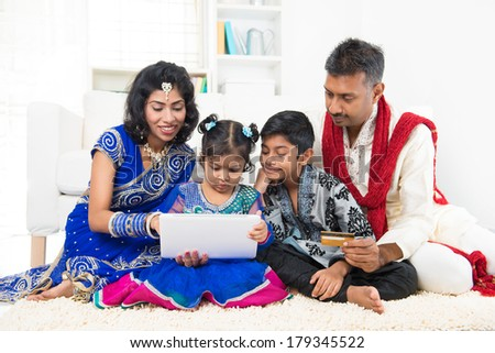 Indian Asian family using tablet pc computer online shopping with credit card at home. India family living lifestyle. Happy smiling parents and children. - stock photo