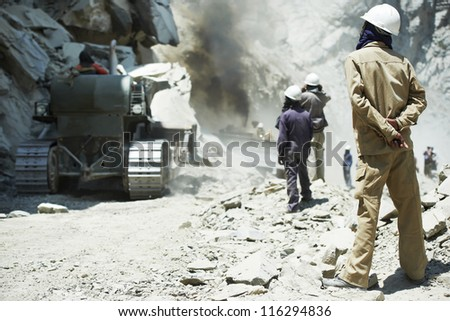 indian asian site manager engineer builder inspecting road  clering at mountains construction site - stock photo