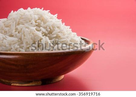 indian basmati rice, pakistani basmati rice, asian basmati rice, cooked basmati rice, cooked white rice, cooked plain rice in wooden bowl over plain colourful background - stock photo