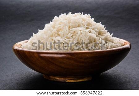 indian basmati rice, pakistani basmati rice, asian basmati rice, cooked basmati rice, cooked white rice, cooked plain rice in wooden bowl over black background - stock photo