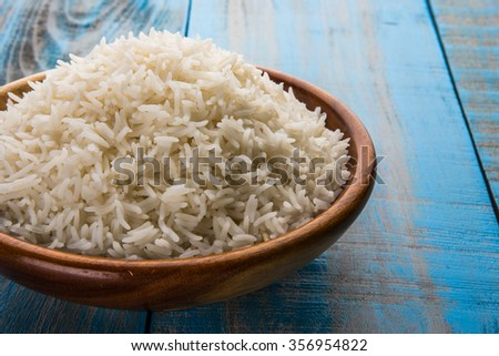 indian basmati rice, pakistani basmati rice, asian basmati rice, cooked basmati rice, cooked white rice, cooked plain rice in wooden bowl overblue wooden background - stock photo