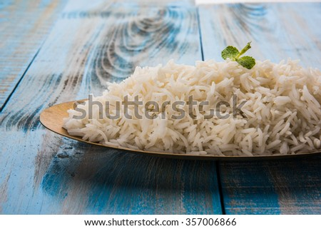 indian basmati rice, pakistani basmati rice, asian basmati rice, cooked basmati rice, cooked white rice, cooked plain rice in oval brass bowl over blue wooden background - stock photo
