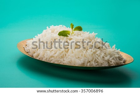 indian basmati rice, pakistani basmati rice, asian basmati rice, cooked basmati rice, cooked white rice, cooked plain rice in oval brass bowl over green background - stock photo